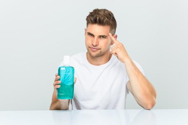 Jeune homme tenant un bain de bouche pointant sa tempe avec le doigt, pensant, concentré sur une tâche.