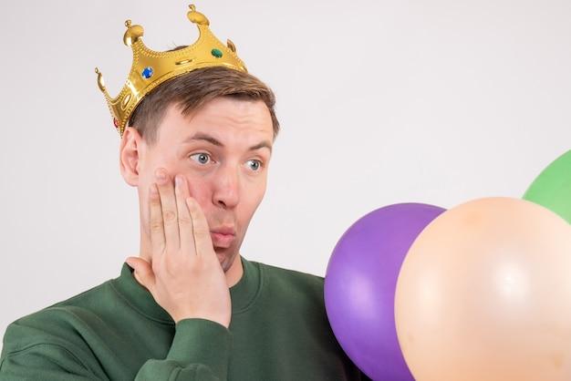 Jeune homme tenant des ballons colorés sur blanc
