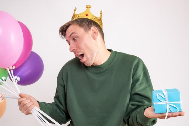 Jeune homme tenant des ballons et peu de cadeau sur blanc
