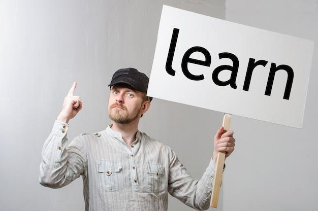 Jeune homme tenant une bannière avec inscription apprendre