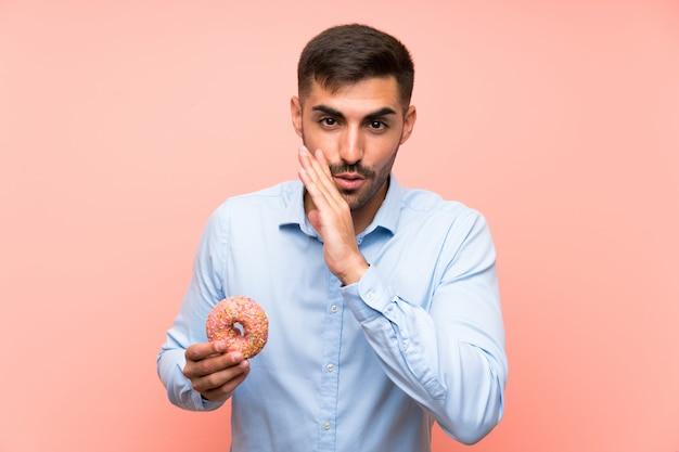 Jeune homme tenant un beignet sur un mur rose isolé murmurant quelque chose