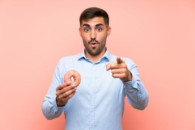 Jeune homme tenant un beignet sur un mur rose isolé surpris et pointant le devant