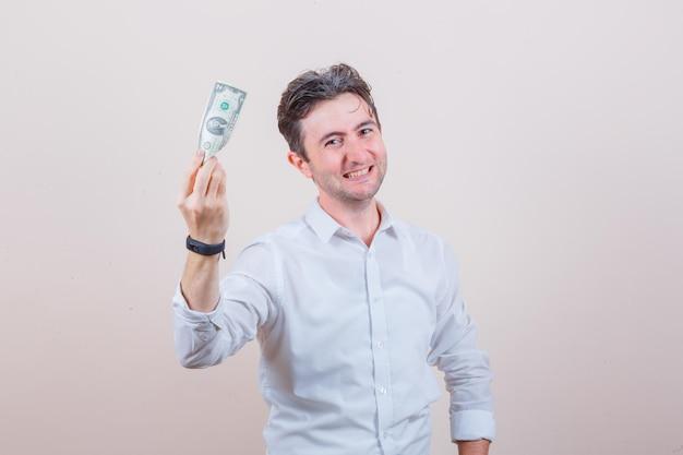 Jeune homme tenant un billet d'un dollar en chemise blanche et semblant joyeux