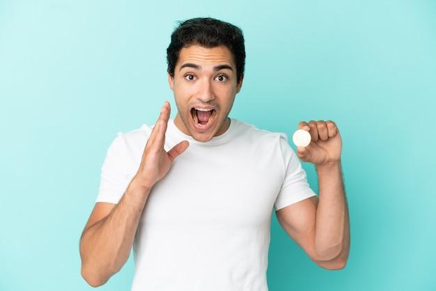 Jeune homme tenant un bitcoin sur fond bleu isolé avec une expression faciale surprise et choquée
