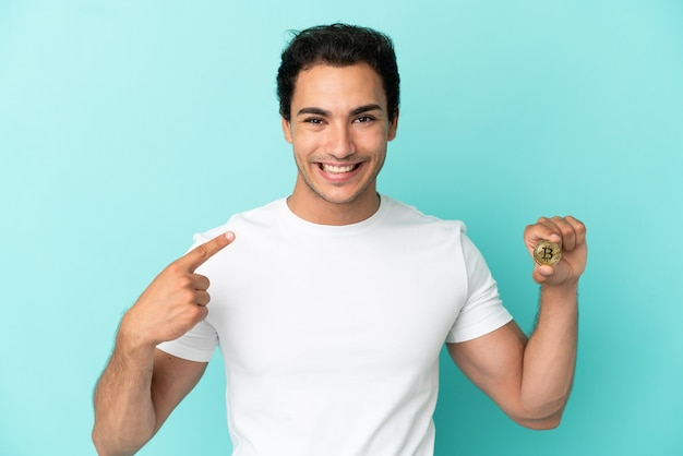 Jeune homme tenant un bitcoin isolé sur fond bleu donnant un coup de pouce geste