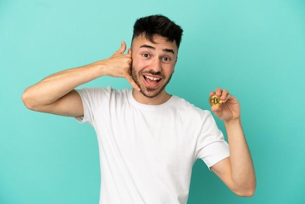 Jeune homme tenant un bitcoin isolé sur fond bleu faisant un geste téléphonique. rappelle-moi signe