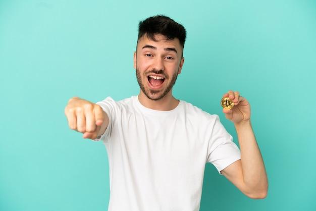 Jeune homme tenant un bitcoin isolé sur fond bleu surpris et pointant vers l'avant
