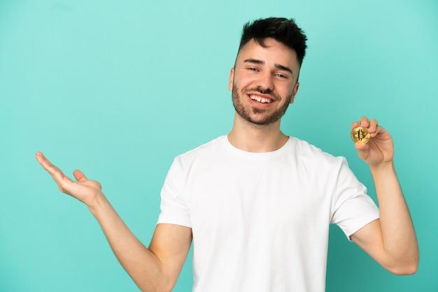Jeune homme tenant un bitcoin isolé sur fond bleu tendant les mains sur le côté pour inviter à venir