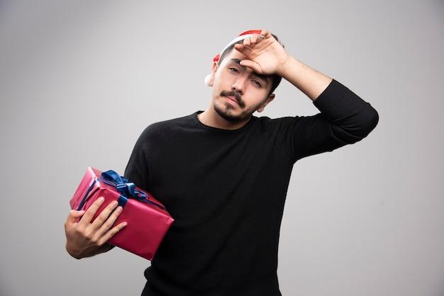 Un jeune homme tenant une boîte-cadeau sur un mur gris.
