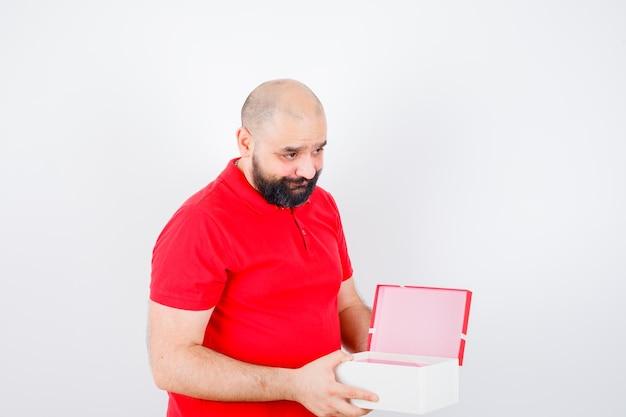 Jeune homme tenant une boîte-cadeau ouverte en t-shirt rouge et l'air timide, vue de face.