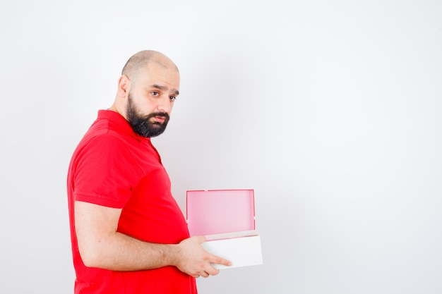 Jeune homme tenant une boîte-cadeau ouverte en t-shirt rouge et ayant l'air réfléchi, vue de face.
