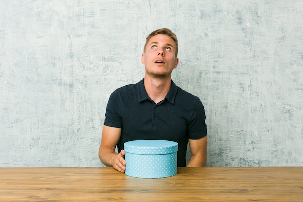 Jeune homme tenant une boîte-cadeau sur une table fatigué d'une tâche répétitive