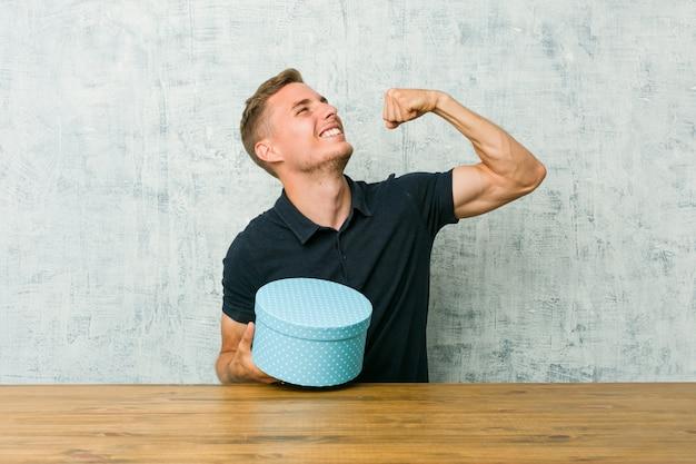 Jeune homme tenant une boîte-cadeau sur une table levant le poing après une victoire