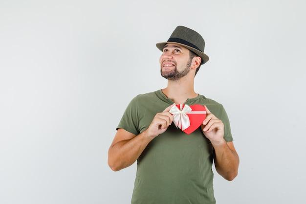 Jeune homme tenant une boîte-cadeau tout en regardant en t-shirt vert et chapeau et à la joyeuse