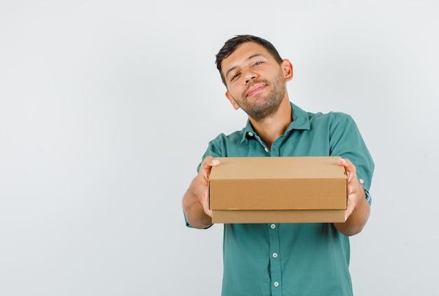 Jeune homme tenant une boîte en carton et souriant en chemise