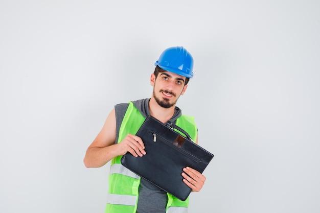 Jeune homme tenant une boîte à outils de construction avec les deux mains en uniforme de construction et ayant l'air heureux