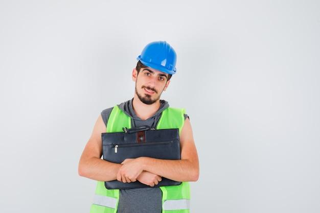 Jeune homme tenant une boîte à outils de construction en uniforme de construction et ayant l'air heureux