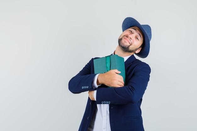 Jeune homme tenant la boîte présente en costume, chapeau et à la recherche de plaisir. vue de face.