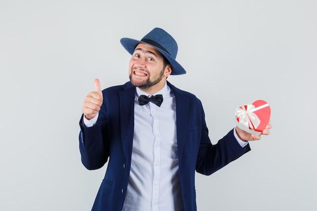 Jeune homme tenant la boîte présente avec le pouce vers le haut en costume, chapeau et regardant heureux, vue de face.