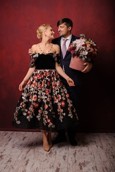 Jeune homme tenant un bouquet de fleurs étreignant sa femme
