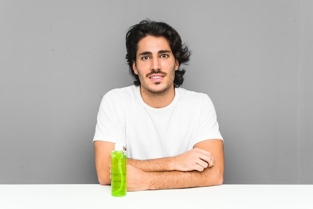 Jeune homme tenant une bouteille d'aloe vera souriant confiant avec les bras croisés.