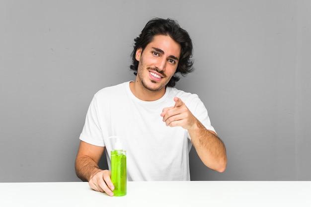 Jeune homme tenant une bouteille d'aloe vera sourires joyeux pointant vers l'avant.