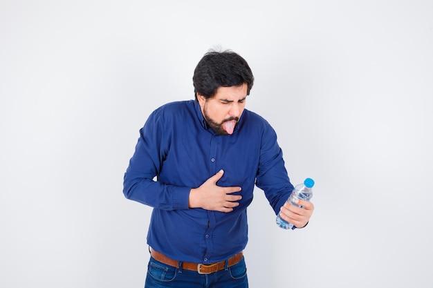 Jeune homme tenant une bouteille d'eau et ayant mal au ventre en chemise bleue et jeans et l'air harcelé. vue de face.
