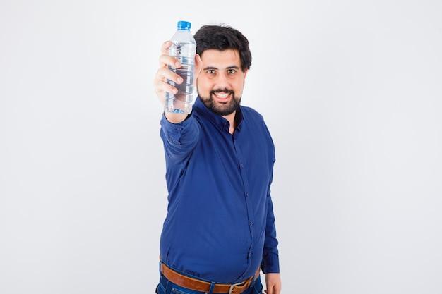 Jeune homme tenant une bouteille d'eau en chemise bleue et jeans et à l'optimisme, vue de face.