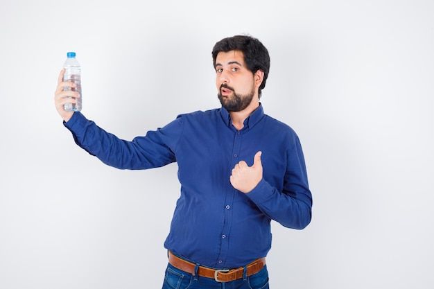 Jeune homme tenant une bouteille d'eau et montrant le pouce en chemise bleue et jeans et à l'optimisme. vue de face.