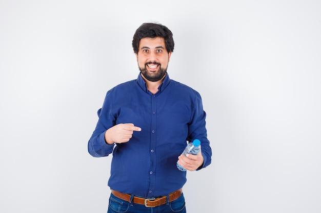 Jeune homme tenant une bouteille d'eau et la pointant en chemise bleue et en jean et l'air optimiste. vue de face.