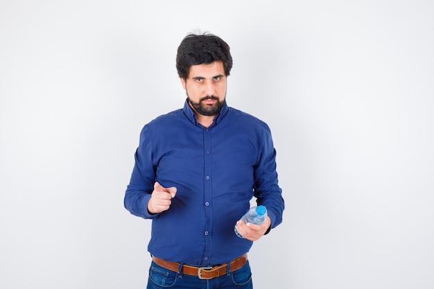 Jeune homme tenant une bouteille d'eau et pointant vers l'avant en chemise bleue et jeans et l'air sérieux. vue de face.