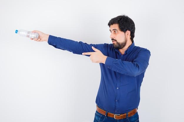 Jeune homme tenant une bouteille d'eau et pointant vers la gauche en chemise bleue et jeans et à l'optimisme. vue de face.