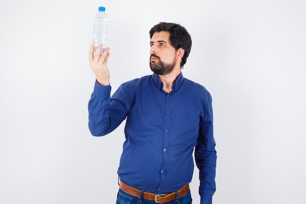 Jeune homme tenant une bouteille d'eau et le regardant en chemise bleue et jeans et l'air sérieux. vue de face.