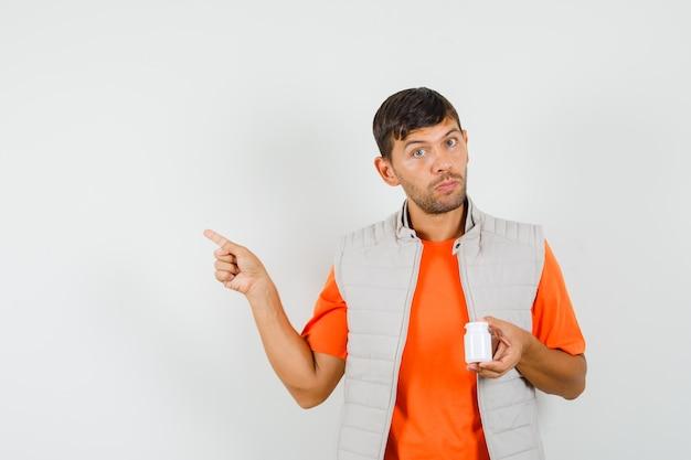 Jeune homme tenant une bouteille de pilules, pointant vers l'extérieur en t-shirt, veste, vue de face.