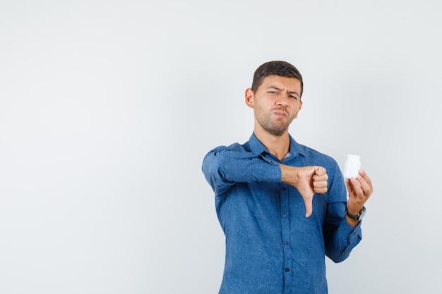 Jeune homme tenant une bouteille de pilules avec le pouce vers le bas en chemise bleue et l'air mécontent. vue de face.