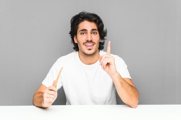 Jeune homme tenant une brosse à dents ayant une excellente idée, concept de créativité.