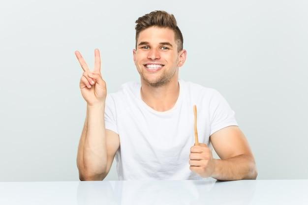 Jeune homme tenant une brosse à dents montrant le numéro deux avec les doigts.