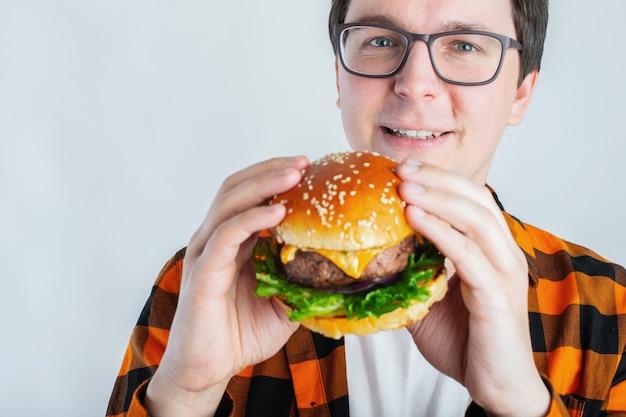 Un jeune homme tenant un burger frais.