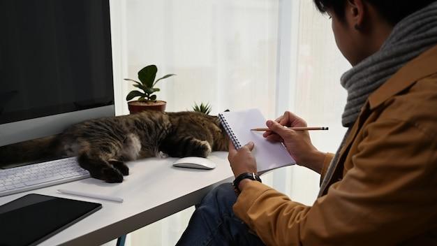 Jeune homme tenant le câblage du stylo sur un ordinateur portable et assis avec un chat mignon dans une maison confortable.