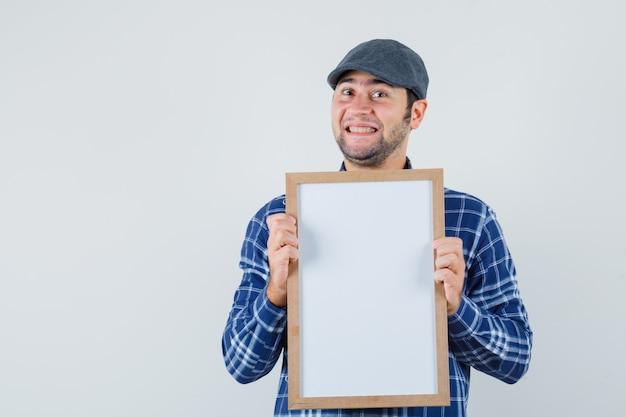Jeune homme tenant un cadre vide en chemise, casquette et à la recherche de plaisir. vue de face.