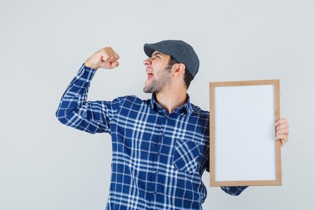 Jeune homme tenant un cadre vide en chemise, casquette et regardant heureux, vue de face.