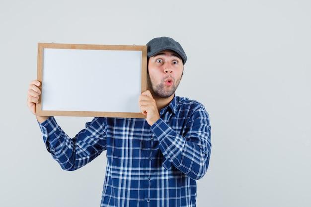 Jeune homme tenant un cadre vide en chemise, casquette et à la surprise. vue de face.