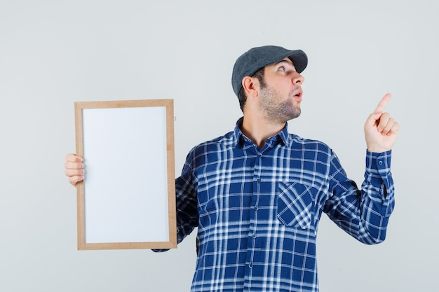 Jeune homme tenant un cadre vide, pointant vers le haut en chemise, casquette et à la surprise. vue de face.