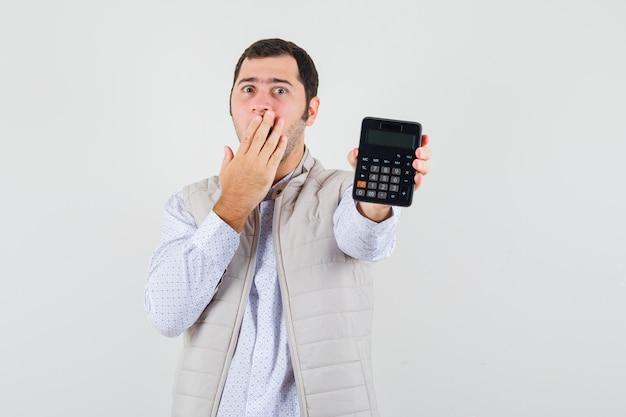Jeune homme tenant la calculatrice dans une main tout en couvrant la bouche avec la main en veste beige et casquette et à la surprise. vue de face.