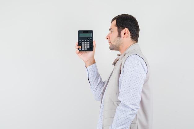 Jeune homme tenant la calculatrice dans une main en veste beige et casquette et à la grave, vue de face.