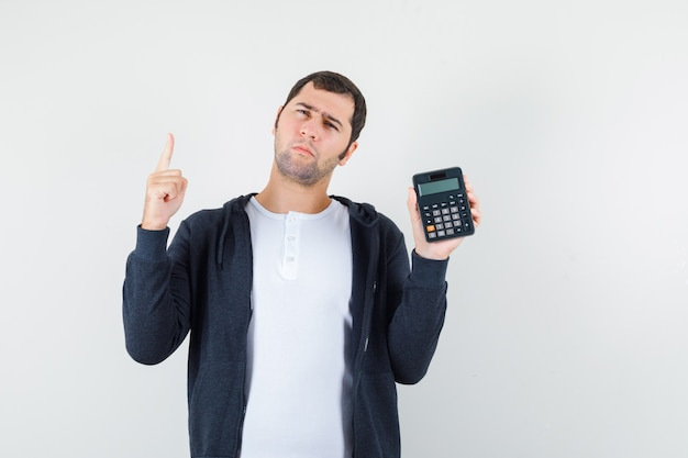 Jeune homme tenant la calculatrice et levant l'index en geste eureka en t-shirt blanc et sweat à capuche noir zippé et regardant pensif. vue de face.
