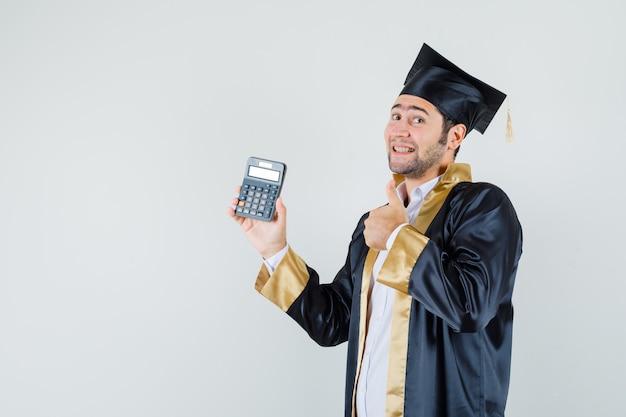 Jeune homme tenant la calculatrice, montrant le pouce vers le haut en uniforme d'études supérieures et à la joyeuse vue de face.