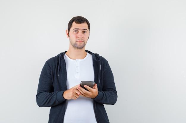Jeune homme tenant la calculatrice en t-shirt blanc et sweat à capuche noir zippé sur le devant et à la vue de face sérieuse
