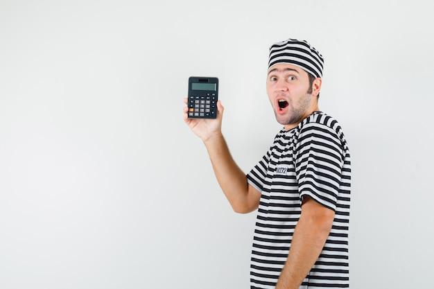 Jeune homme tenant la calculatrice en t-shirt, chapeau et à la surprise.