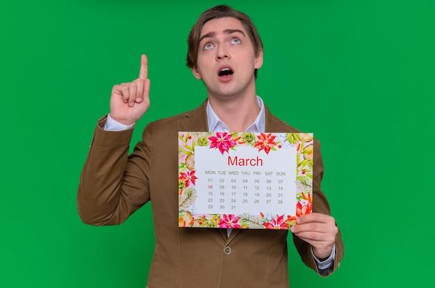 Jeune homme tenant le calendrier papier du mois de mars à la recherche de surprise montrant l'index journée internationale des femmes concept de mars